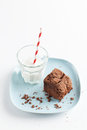 Chocolate brownie on plate served with milk slice of delicious homemade pale blue glass of red white stripe straw Stock Photo