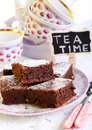 Chocolate brownies dusted with icing sugar on plate and a sign saying tea time Stock Images