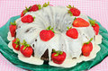 Chocolate bundt cake frosted with vanilla cream and decorated with fresh strawberries served on green platter against pink gingham Stock Photos