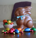 Chocolate bunny with easter eggs on table rabbit blue ribbon and Stock Photos