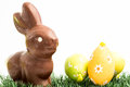 Chocolate bunny rabbit three easter eggs grass white background Stock Image