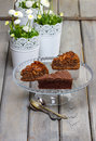 Chocolate cake on glass stand grey wooden table daisy flowers in white flower pots in the background Stock Photo