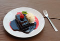 Chocolate cake and ice cream with cherry topping Royalty Free Stock Photos