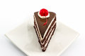 Chocolate cake slice with red cherry fruit on white plate Stock Photos