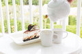 Chocolate cake with tea set in garden Royalty Free Stock Photo