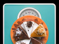 Chocolate cake on weigh-scale Royalty Free Stock Photo