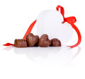 Chocolate candies and White gift in form of heart Stock Photos