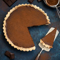 Chocolate and caramel tart on dark blue background Royalty Free Stock Photo