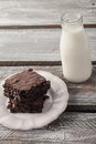 Chocolate chip brownie decadent dark with a milk jug on a weathered barn wood table Stock Photography