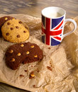 Chocolate chip cookies milk union jack mug white and dark with in english flag on crumpled light brown paper Royalty Free Stock Photo