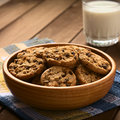 Chocolate chip cookies with milk in wooden bowl a glass of cold in the back photographed on cloth on wood natural light Royalty Free Stock Photography