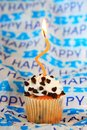 Chocolate chip happy birthday cupcake with orange wavy candle Royalty Free Stock Photos