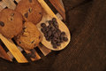 Chocolate chips cookies three on a wood cooling rack with some placed beside on a wooden spoon view from the top Stock Photo