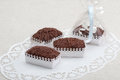Chocolate cookies in decorative boxes on a white ornamental table cloth napkin Royalty Free Stock Image