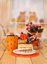 Chocolate cream cake, cup tea, slice, candle on background kitchen. Royalty Free Stock Photo