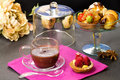 Chocolate cup with fancy cakes and floral decorations confectionery Royalty Free Stock Images