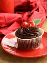 Chocolate cupcake with cherries and cream on a red plate Royalty Free Stock Image