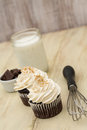 Chocolate cupcakes with milk and wisk white vanilla frosting glass of pieces of vertical Stock Image