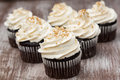 Chocolate cupcakes with vanilla buttercream frosting and gold sprinkles Stock Photo