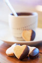 Chocolate dipped heart shaped cookies and cup of coffee on wooden table Royalty Free Stock Photography