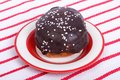Chocolate donut on a plate against a striped tablecloth Royalty Free Stock Photography