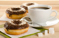 Chocolate donuts with coffee and sugar on the wooden table Stock Image