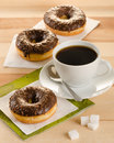 Chocolate donuts with coffee and sugar on the wooden table Stock Photos