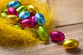 Chocolate easter eggs yellow nest wooden table background holiday composition Royalty Free Stock Photography