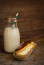 Chocolate eclair in a paper and an old fashion bottle of milk on a wooden surface Royalty Free Stock Photography