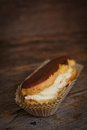 Chocolate eclair in a paper on a wooden surface Royalty Free Stock Images