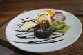chocolate lava cake set served with ice cream vanila,wiped and mix fruit on white plate,process color Royalty Free Stock Photo