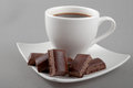Chocolate lies on a saucer with black coffee Stock Images
