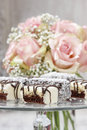 Chocolate and marzipan cakes on glass cake stand bouquet of pink roses in the background Royalty Free Stock Photos