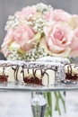 Chocolate and marzipan cakes on glass cake stand bouquet of pink roses in the background Royalty Free Stock Images