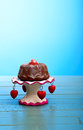 Chocolate mini pound bundt cake with strawberry and icing suga on top sugar on antic stand red hearts on rustic turquoise table Royalty Free Stock Photo