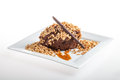 Chocolate mousse dessert with nuts caramel stick on a white plate white background Stock Images