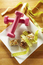 Chocolate muesli bars with measuring tape and weights Stock Photos
