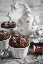 Chocolate muffins and ceramic Santa Claus on a light wooden surface Royalty Free Stock Photo