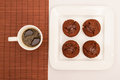 Chocolate muffins with a cup of coffee on white plate Royalty Free Stock Images