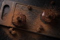 Chocolate muffins, decorated with a small cone on a dark wooden background. Cupcakes are poured with dark chocolate and cocoa powd