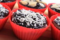 Chocolate muffins with desiccated coconut and sliced almonds homemade delicious fresh baked in red silicone cups lying on wooden Royalty Free Stock Images