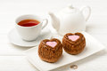 Chocolate muffins in shape of heart and cup of tea on wooden table. Royalty Free Stock Photo