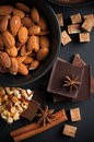 Chocolate nuts sweets spices and brown sugar black milk on a black background food concept Royalty Free Stock Photo
