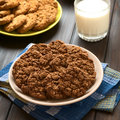 Chocolate oatmeal cookies on plate with a glass of milk and apple in the back photographed with natural light Stock Photos