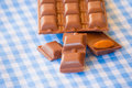 Chocolate pieces with almond on a blue tablecloth Stock Photos