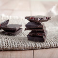 Chocolate pieces tower on a wooden surface close up Royalty Free Stock Images