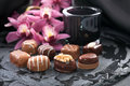 Chocolate pralines on black stone surface decorated with with orchids Royalty Free Stock Photos