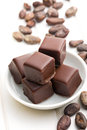 Chocolate pralines with cocoa beans on white table Stock Images