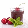 Chocolate sauce and cherry on wood Royalty Free Stock Photos