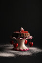 Chocolate sponge cake with strawberry and icing sugar on stand w slices top antic red hearts Royalty Free Stock Images